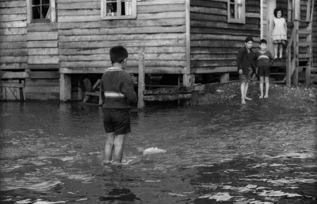Fotografìa de niños descalsos sobre el agua, inundación en ciudad de la unión